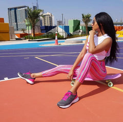 Woman sitting on skateboard wearing colorful leggings