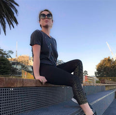 Woman sitting on a step wearing black and gold glitter leggings