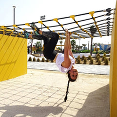 Woman hanhing upside down on monkey bars wearing black leggings