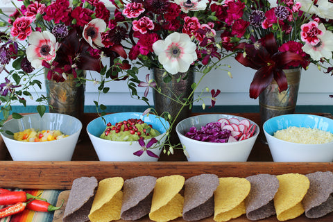 Image of four handblown glass bowls from Serve Kindness filled with taco makings along with beautiful flowers in background. Photo by @studionectar