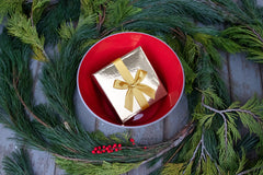 Red Kindness Bowl filled with small gold wrapped present