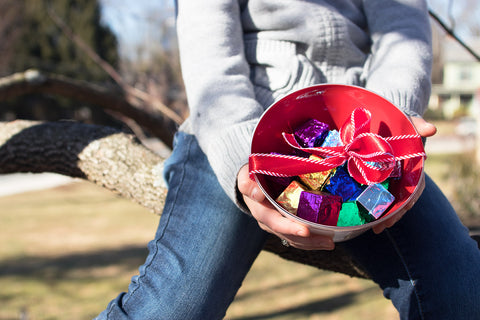Vibrant red hand blown glass bowl filled with chocolates for a beautiful valentine's day gift.