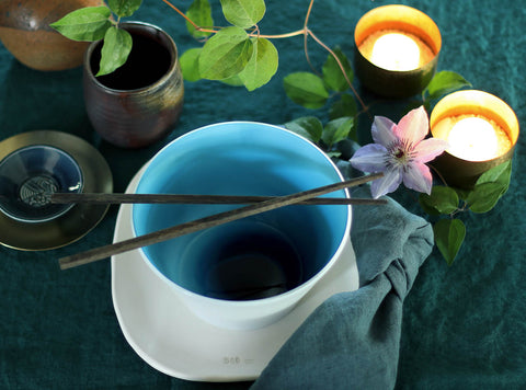 Image of aquamarine blue handblown glass bowl from Serve Kindnewss with chopsticks on top and candles