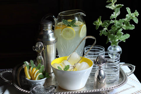 Silver tray with lemonade pitcher and yellow handblown glass bowl from Serve Kindness. Photo by @studionectar