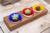 Handblown glass bowls from Serve Kindness in cobalt blue, red, and gold colors set in a 3 hole wood tray