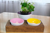 Handblown glass bowls from Serve Kindness in yellow and pink colors set in a 2 hole wood tray