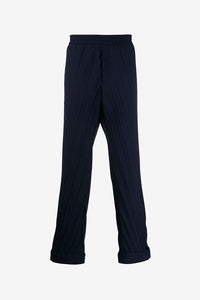 Pleated navy colored trousers with flowy legs and elastic waistband