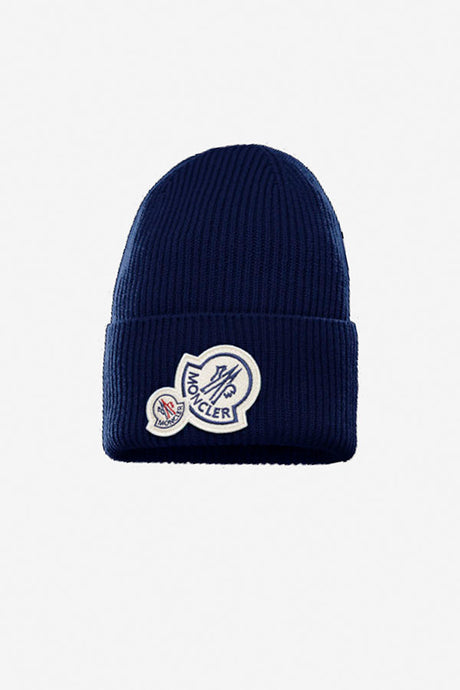 Blue beanie in a rib-knit made from virgin wool and cashmere. The beanie has a double fold turn-up and the front carries a large brand logo in a light felt.