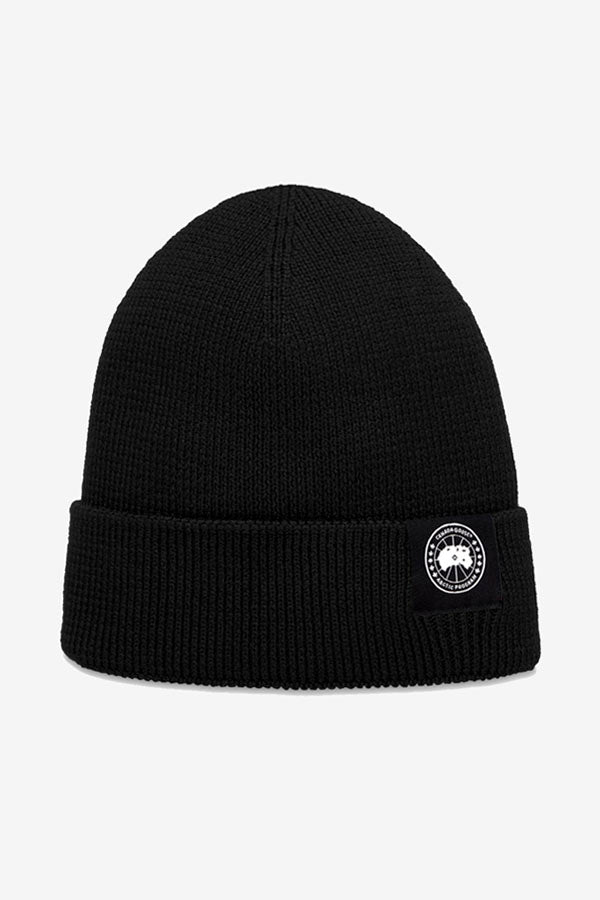 Beanie in black ribbed wool, with a turn-up. On the front is a patch logo in black and white, holding the Canada Goose graphic.