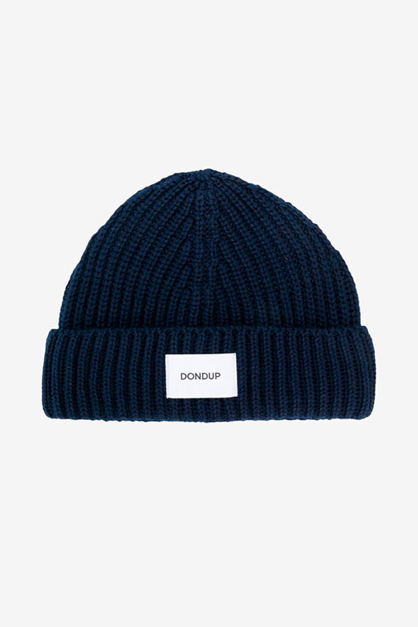 Beanie in ribbed navy wool blend, with a turn up hem and patch logo in white.