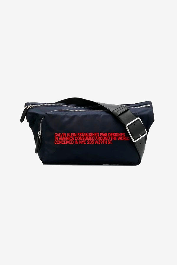 Belt bag in blue with red embroidery logo on the front and one large main compartment and one smaller.