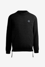 Knitwear in black. The bottom side seam has a zipper opening. The chest holds a black label logo and at bottom a kangaroo pockets.