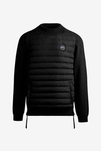 Down filled body with knit sleeves in black. The bottom side seam has a zipper opening. The chest holds a black label logo and at bottom a kangaroo pockets.
