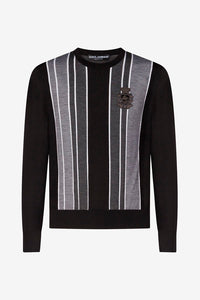 Sweater in black with a grey and white striped pattern on the front, with a DG patch logo. It has long sleeves and a round neck.