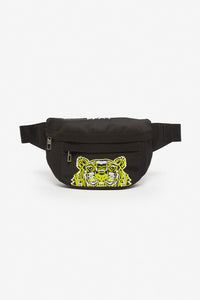 Belt bag in black from Kenzo, with a Kenzo logo on top in embroidered white. Tiger logo on the front in embroidered yellow, white and black