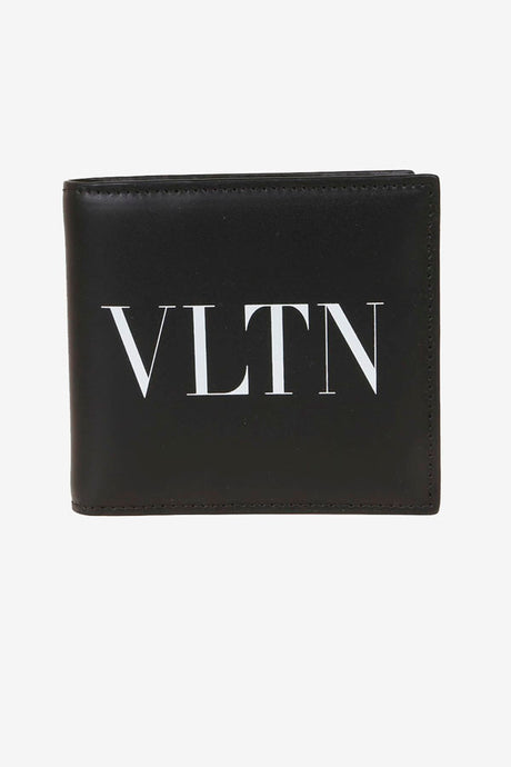 Black wallet in calfskin, in a square shape. On the front is VLTN printed on white, inside holds eight card slots.