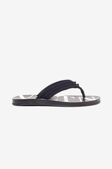 Flip flops with VLTN logo at the sole