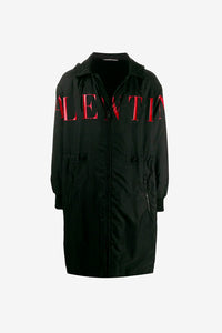 Long raincoat from Valentino, made from a black polyamide with a red Valentino graphic across the front. Features a front zipper fastening, hood and two front pockets with zipper fastening.