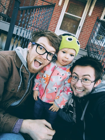 Two men and their daughter smiling.