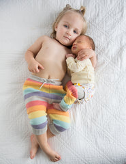 Kids laying down on bed in rainbow cloth diaper