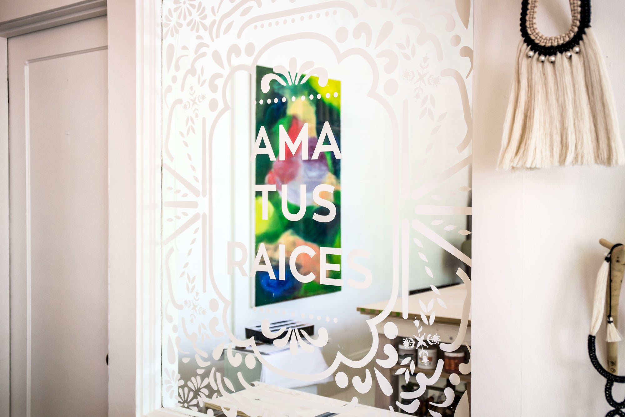 Ama Tus Raices window decal inside Vía Raíz shop