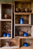 small wood planters and blue enamel mugs and coffee pitcher displayed in wood crates