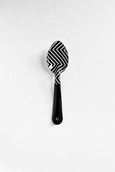 black and white enamel spoon with graphic pattern