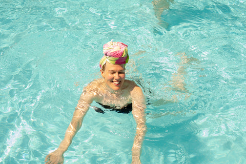 Girl in bikini in swimming pool with Hamamingo Carnival Travel Towel wrapped on head like a turban