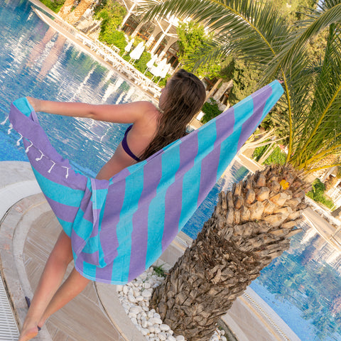 Girl by pool with Hamamingo Carnival Travel Towel flowing behind her