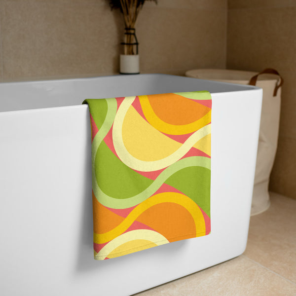 "Mid Century Modern Citrus SunKissed 30"" x 60"" Beach & Pool Towel folded on a tub"