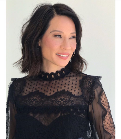 Lucy Liu smiling and looking to the side in black lace top