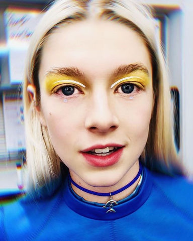 Jules from Euphoria wearing neon yellow eyeshadow and blue top.