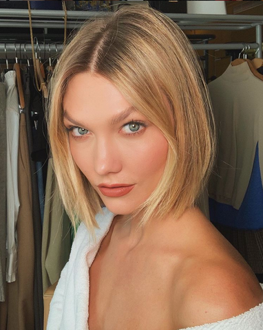 Karlie Kloss is photographed in glam makeup and blown out hair.