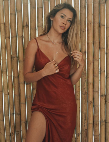 Caelynn Miller-Keyes takes a picture wearing a deep red silk dress.