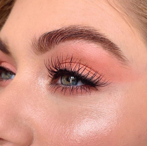 A close up shot of a model's eye wearing blush as eyeshadow.