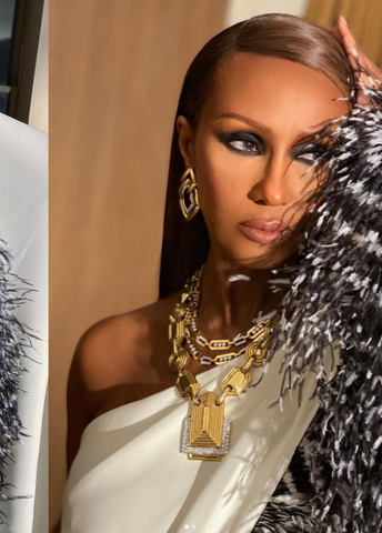 Iman poses wearing glam makeup, a white top, and a black and white coat.