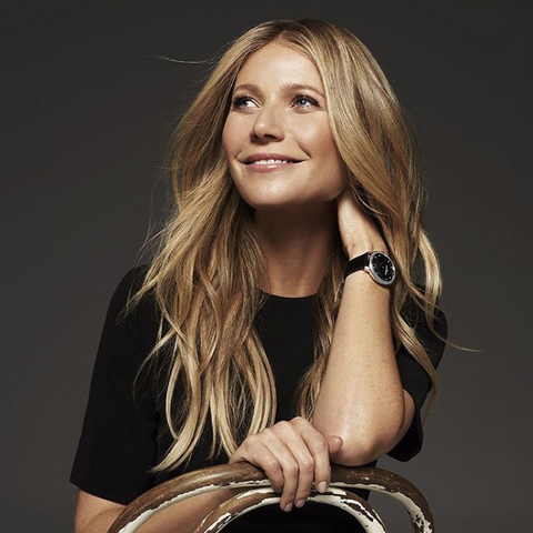 Gwyneth Paltrow is photographed in a studio with blown out hair and natural makeup.