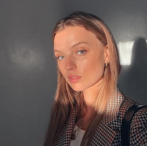 Amanda Mondale takes a picture in a shadowy light with natural makeup on.