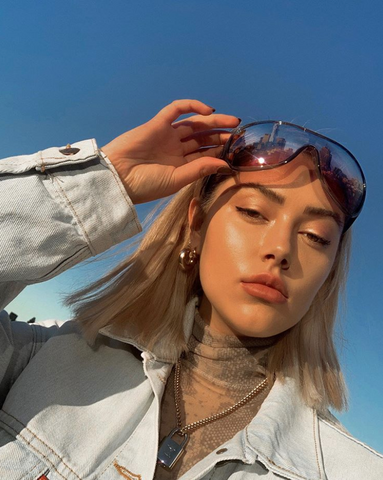 Jourdan Sloane takes a picture outside wearing sunglasses and a jean jacket with glowy makeup.