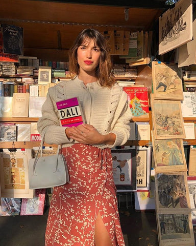 Jeanne Damas stands in front of a book stand in paris wearing a long red skirt and a cream sweater.