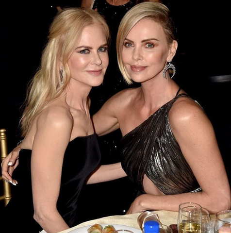 Charlize Theron and Nicole Kidman take a picture together sitting down at the Academy Awards Ceremony