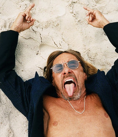 Iggy Pop takes a picture laying in the sand with his tongue out