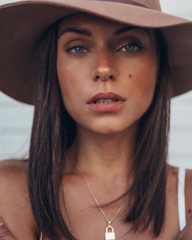 Alyssa Lynch is photographed wearing a hat and Kristofer Buckle makeup