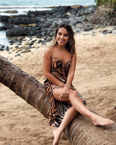 Lital Vardi sits on a palm tree at the beach wearing a zebra silk dress.