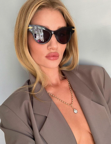Rosie HW wears sunglasses and a blazer with beautiful facial makeup.