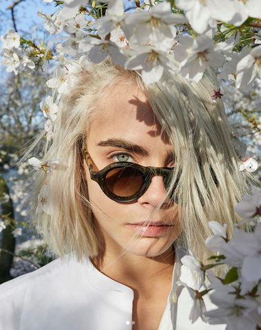 Cara Delevinge is candidly photographed through a tree of white flowers as she wears sunglasses and a white top.
