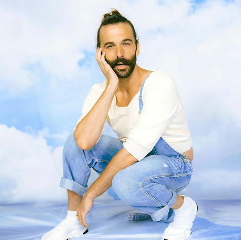 Johnathan Van Ness squats down wearing overalls and a white long sleeve shirt in front of a sky backdrop