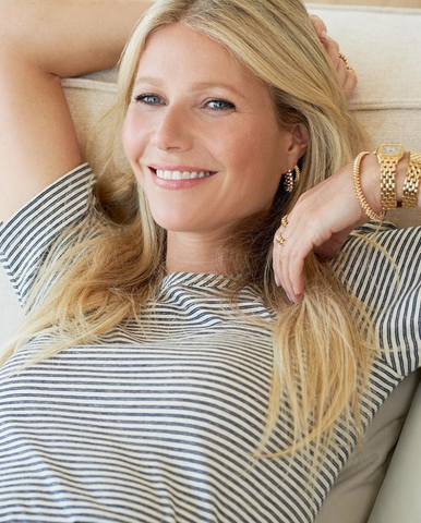 Gwyneth Paltrow sits on couch wearing a striped t-shirt and gold jewelry.