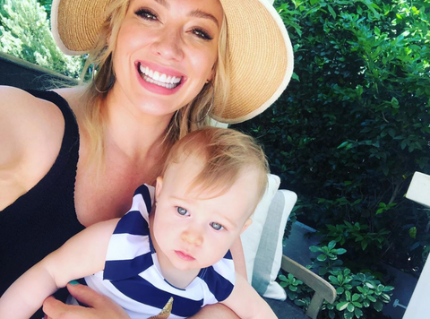 Hilary Duff wears a black tank top and straw hat as she takes a picture with her baby.
