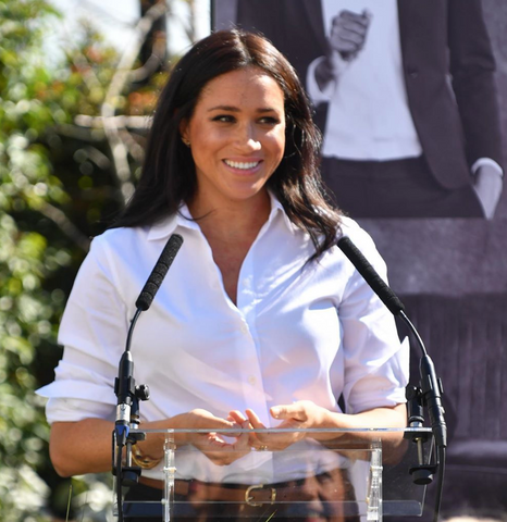 Meghan Markle makes a speech wearing a white button up shirt and natural makeup.